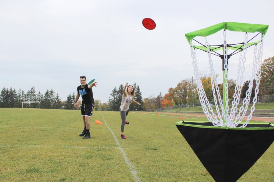 Ryan Heim and Haley Sedore try their hand at disc golf Tuesday during Try Day at Orillia Secondary School. Nathan Taylor/OrilliaMatters