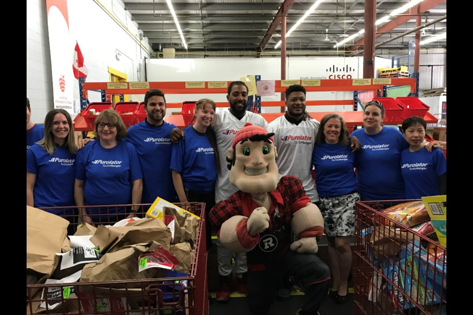 Defensive Lineman Jonathan Newsome and Linebacker Kevin Brown II (centre) posing with Ottawa Food Bank volunteers and the Redblacks mascot during the food sorting challenge.  Photo/ Brian Findlay