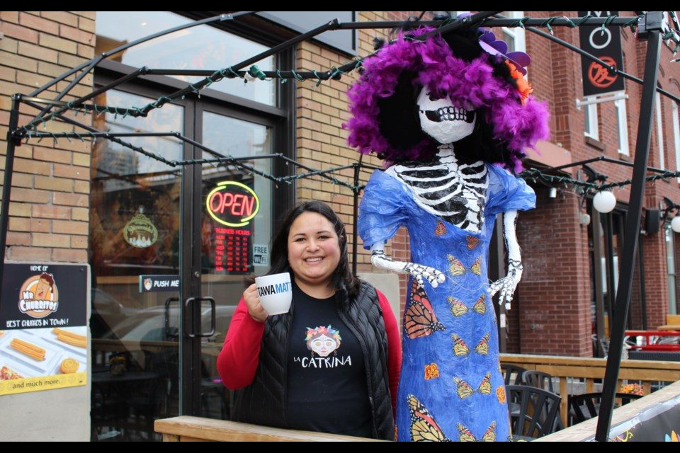 "Co-owner Diana Martinez-Ortega stands next to ""La Catrina"", the namesake of her and her husband's new café in the ByWard Market. Drew May/OttawaMatters.com"