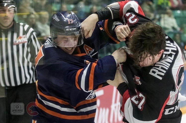 Rhett Rhinehart (#27) gets into a scrap against a Kamloops Blazer at the CN Centre (via Prince George Cougars/James Doyle Photography)