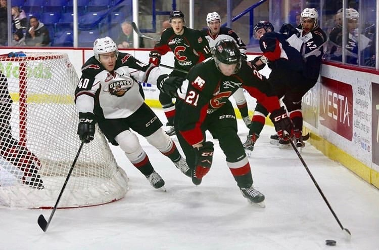 Connor Bowie (#21) carries the puck behind the net in a road game for the Prince George Cougars against the Vancouver Giants (via Vancouver Giants/Rik Fedyck Photography)