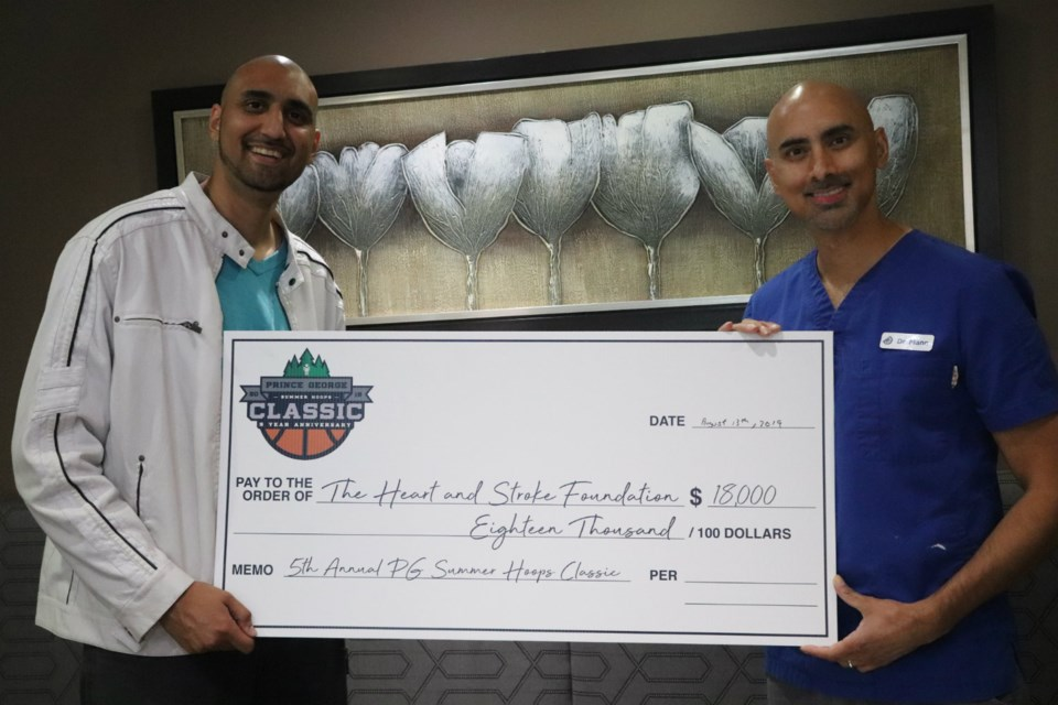 Prince George Summer Hoops Classic Organizer Nav Parmar (left) stands proudly with cousin Dr. Nav Mann, holding a cheque for $18,000 to the Heart and Stroke Foundation of Canada (via Kyle Balzer)