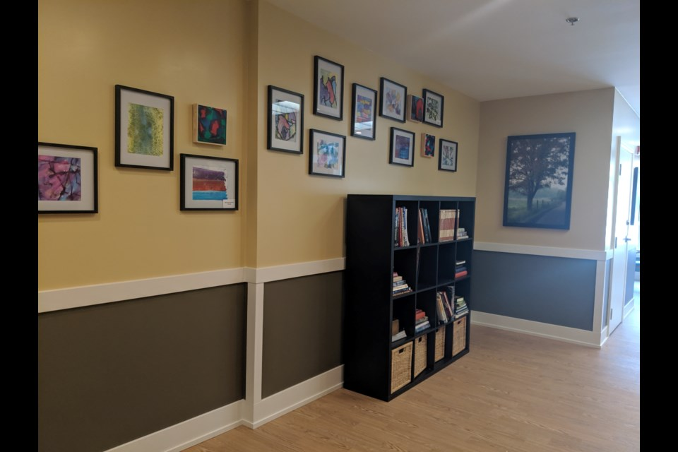 A hallway with artwork and a book shelve mimics the feeling of home.