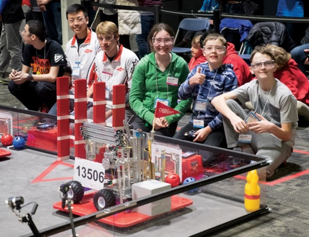 Our Lady of the Snows Catholic Academy team with their robot #13506 before the start of a round. From right to left are Oliver Langhorst (grey), Thomas Paul and Erin Berry.