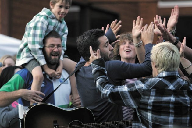 Michael Bernard Fitzgerald greets the enthusiastic crowd following the Canmore Folk Music Festival's Friday Night Street Party at the Canmore Civic Centre.