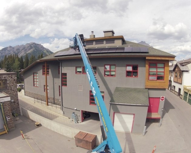Workers install solar panels on Banff Town Hall in 2013 in a move to reduce energy consumption and greenhouse gas emissions.