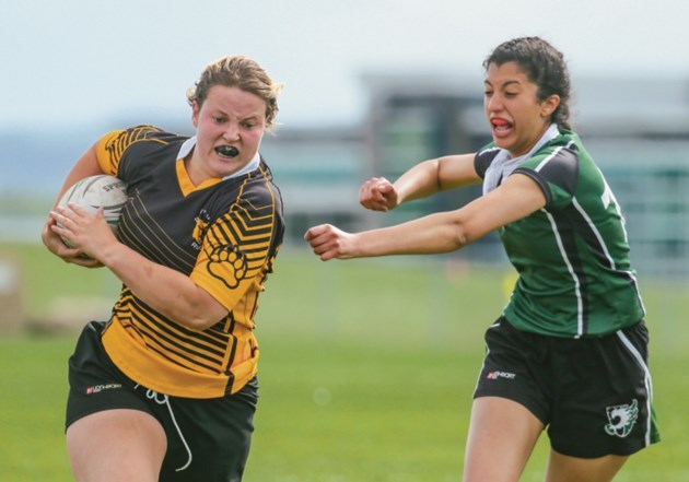 Banff Bears player Holly Phillips, left, deftly evades an attempt by Springbank to tackle at the Calgary Rugby Union on Thursday (June 1). Phillips was selected to Canada's
