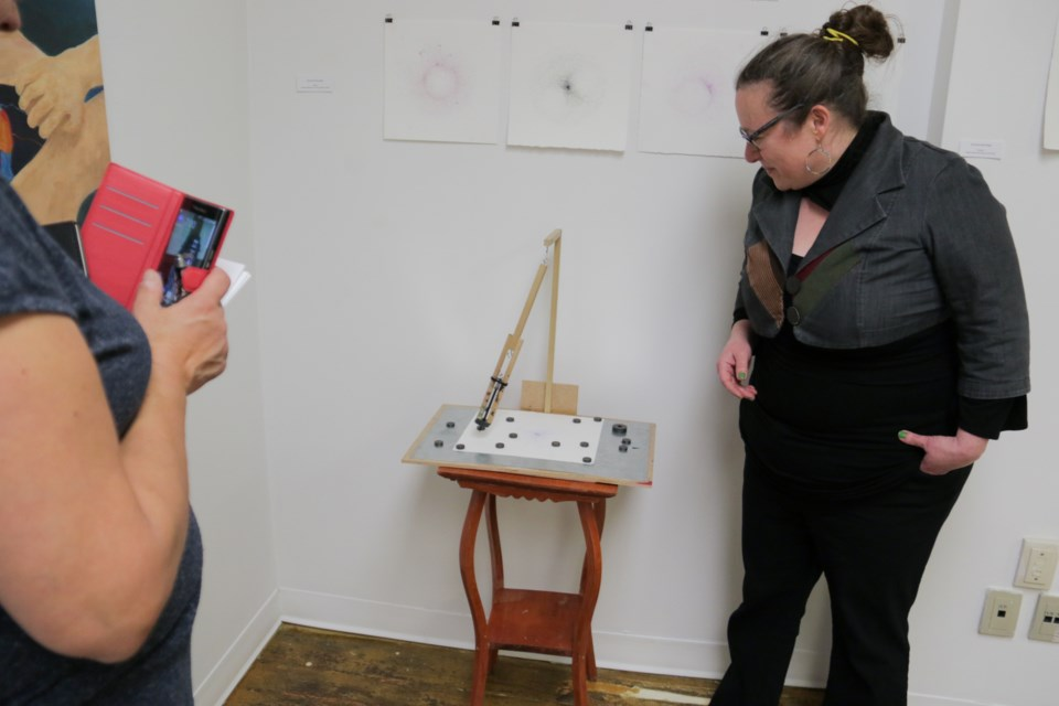 Miinikaan Project project liaison Isabelle Michaud uses exhibiting artist Kyrstiana Bourdage's 'Pulse' prototype drawing device at the Dawaa Dazhi Gallery opening on Saturday. Jeff Klassen/SooToday
