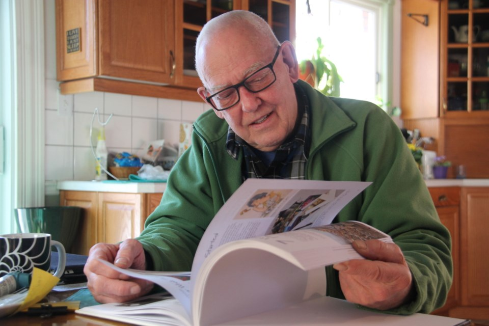 Sault artist Gordon MacKenzie in his home, looking over his latest art instruction book, entitled The Watercolorist's Essential Notebook - Keep Painting!, Jan. 12, 2018. Darren Taylor/SooToday