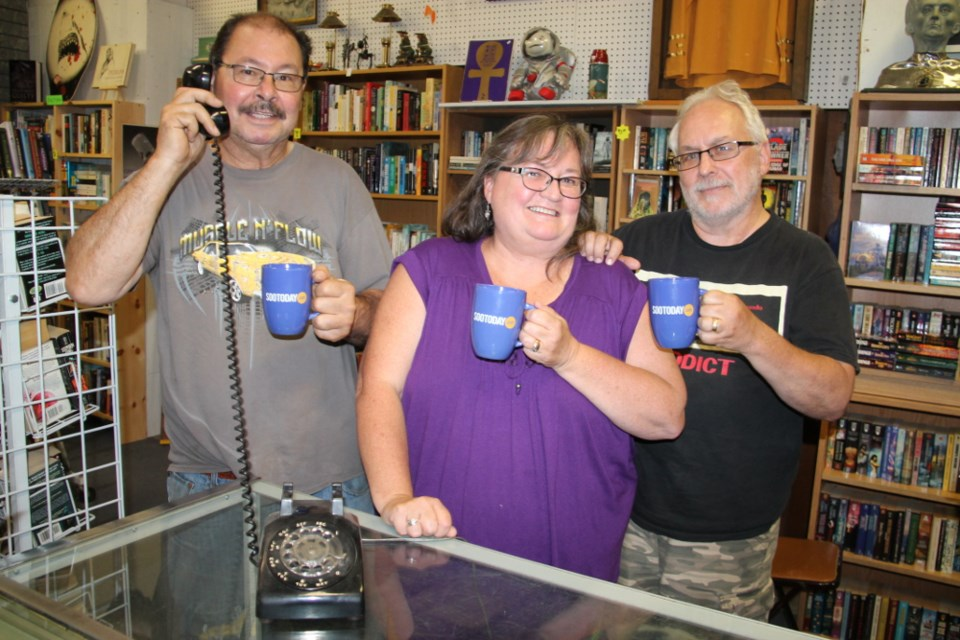 Bill Gay 'makes a call' with a collectible phone, with Donna and Bob Berry.  The three chatted about their Books and Collectibles store located at 137 Gore Street, receiving SooToday mugs as the subject of this week's SooToday Mid-Week Mugging, Aug. 23, 2017. Darren Taylor/SooToday