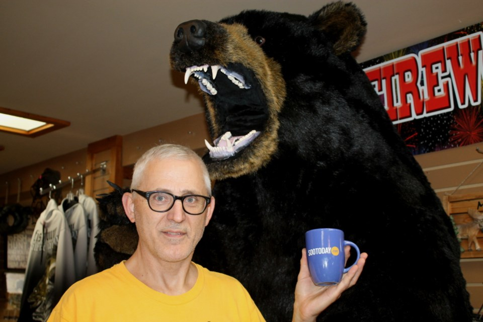 Orest Witiw, Trading Post co-manager, with a SooToday coffee mug and giant, furry friend, Sept. 6, 2017. Darren Taylor/SooToday