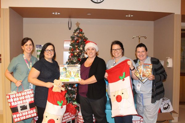 Amanda Johnston and Heather Hilderley-Phillips, second and third from left, delivered over $9,000 in gifts to sick children and their parents at Sault Area Hospital on Friday, Dec. 23, 2016. Photo supplied.