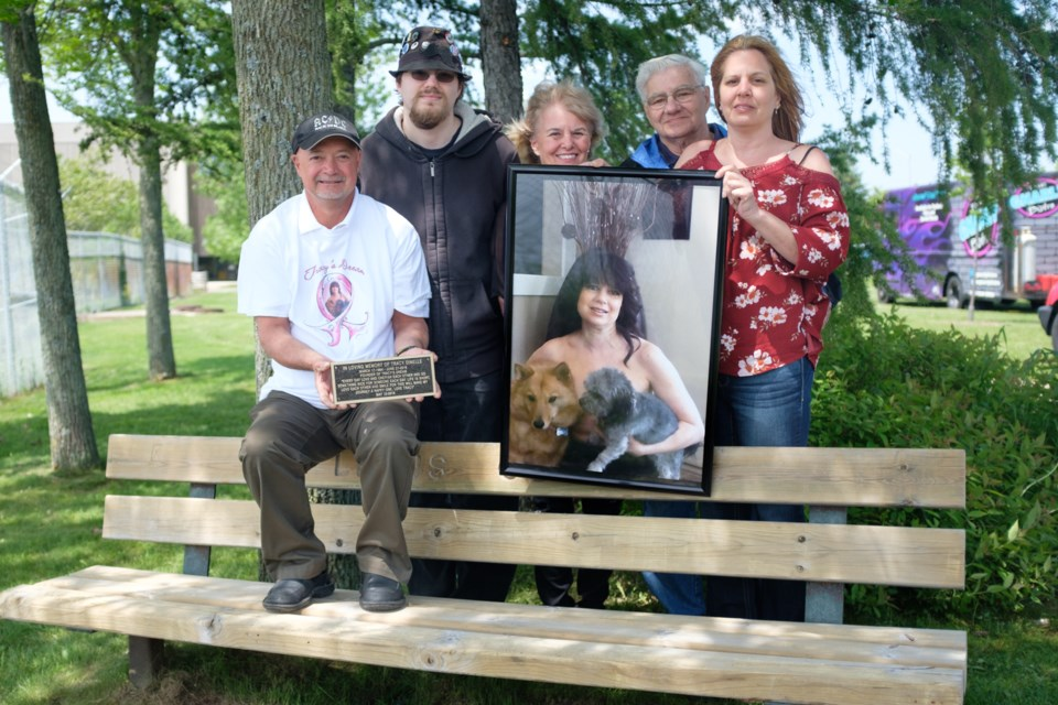 The family of Tracy Dinelle holding her image on the bench that was dedicated to her on Saturday. (From left) husband Dennis Dinelle, son Tyler Dinelle, mother Rena Ross, father Jackie Particelli, and sister Carla Particelli. Carla and Jackie were both diagnosed with cancer within just two years of Tracey. Jeff Klassen/SooToday