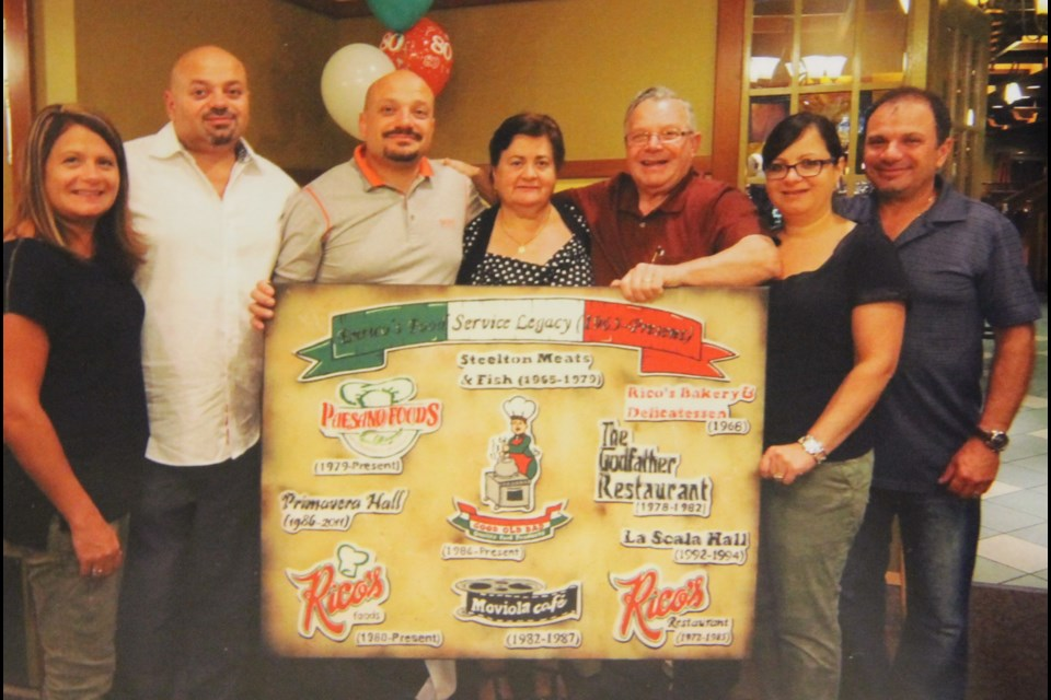 Enrico Ianni-Palarchio and family with a board showing the logos of all the businesses he started in Sault Ste. Marie. Photo provided