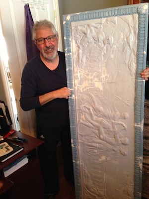 Alex Solomon with one of the decorative wall hangings that hung in the former Palace Theatre in Blind River. Kris Svela for ElliotLakeToday