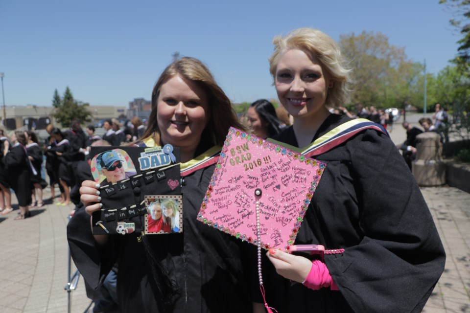 Erica Kennis (left) and Brittney Drouin (right) before the Algoma University Convocation ceremony on Saturday. Friends and classmates for six years, Kennis and Drouin lost their fathers on the same day in April this year. Photo by Jeff Klassen for SooToday