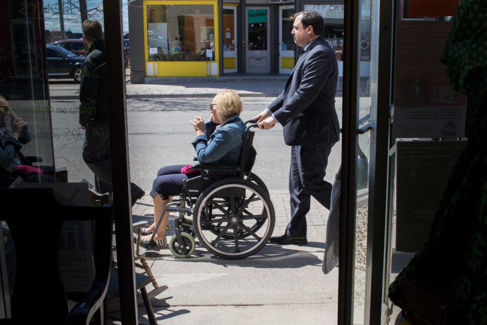 Mayor Christian Provenzano pushes a person in a wheelchair along Queen Street during the Accessibility in Downtown Sault Ste. Marie Walk as part of the 2017 Jane's Walk Sault Ste. Marie multi-tour event. Event organizers invited users to sit in and push wheelchairs so they could get a better understanding of the mobility issues some people face downtown. Jeff Klassen/SooToday