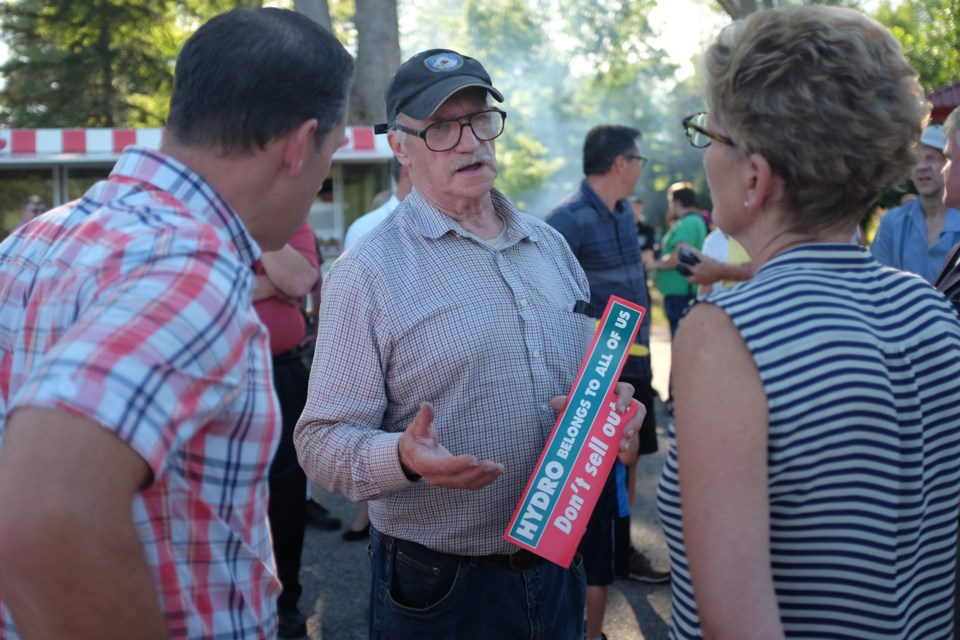 Ontario Premier Kathleen Wynne and Sault MPP David Orazietti held a barbecue and community meet and greet at Bellevue Park Monday evening as was part of their weeklong Northern Ontario tour. Ted Hallin-Williamson was able to get face time with the pair while holding an anti-privatization of Hydro One sticker. Jeff Klassen/SooToday