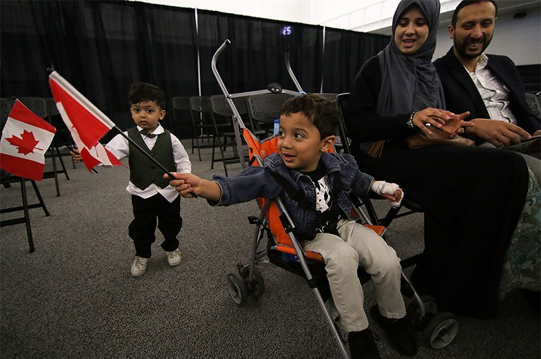 Children wave Canadian flags immediately prior to a citizenship ceremony as part of Passport to Unity on May 1, 2015 at Sault College. Kenneth Armstrong/SooToday