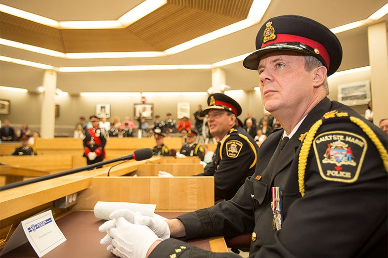 Outgoing Police Chief Bob Davies listens to a speaker during the swearing-in of the Police Chief Bob Keetch June 16, 2014 in Sault Ste. Marie, Ont. SooToday.com/Kenneth Armstrong
