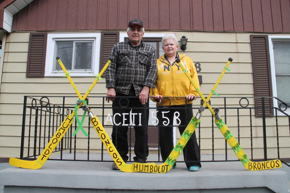 Tony and Rose Aceti on the steps of their Douglas Street home, with a memorial scene Tony constructed using the sticks of his deceased goalie son TJ Aceti, May 3, 2018. Darren Taylor/SooToday