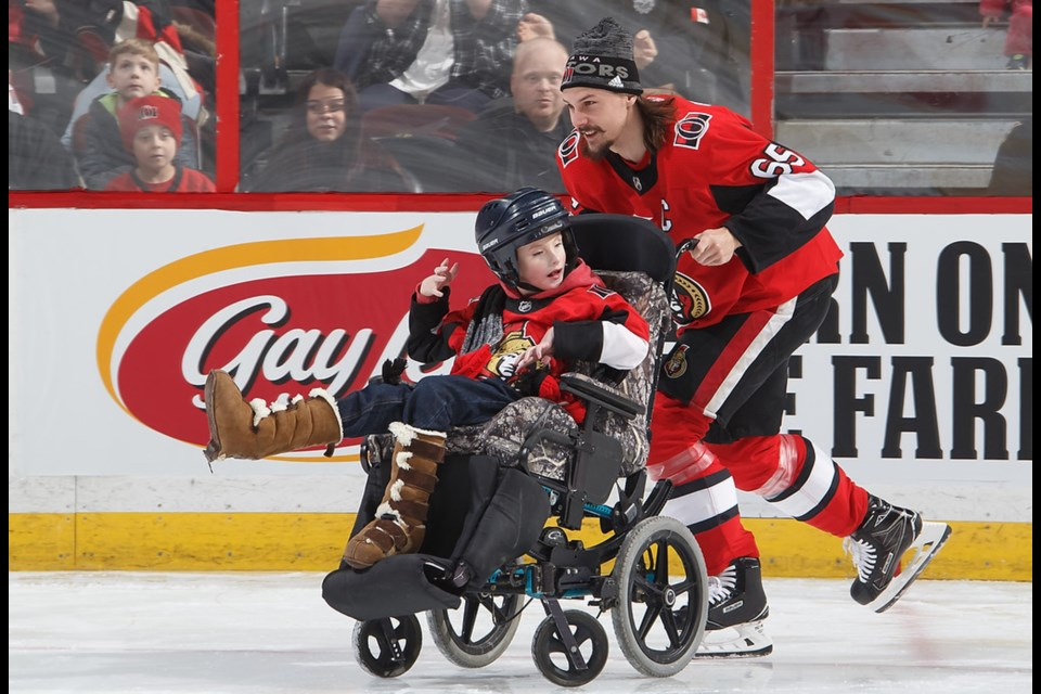 Billy 'Dozer' Adam is taken for a spin by Ottawa Senators captain Erik Karlsson during Sunday's 'Sen Skills' competition. Photo courtesy of Ivy Adam and Ottawa Senators