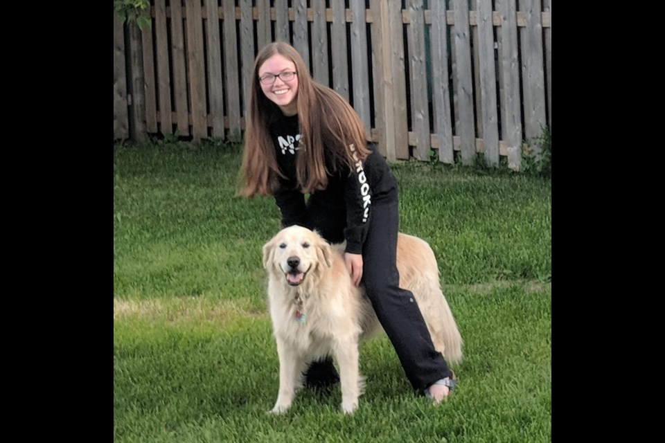 Sarah Nelson, now 15 and retired from her baking business, seen in a recent photo with her dog Macker Boy. Photo provided by Sarah Nelson