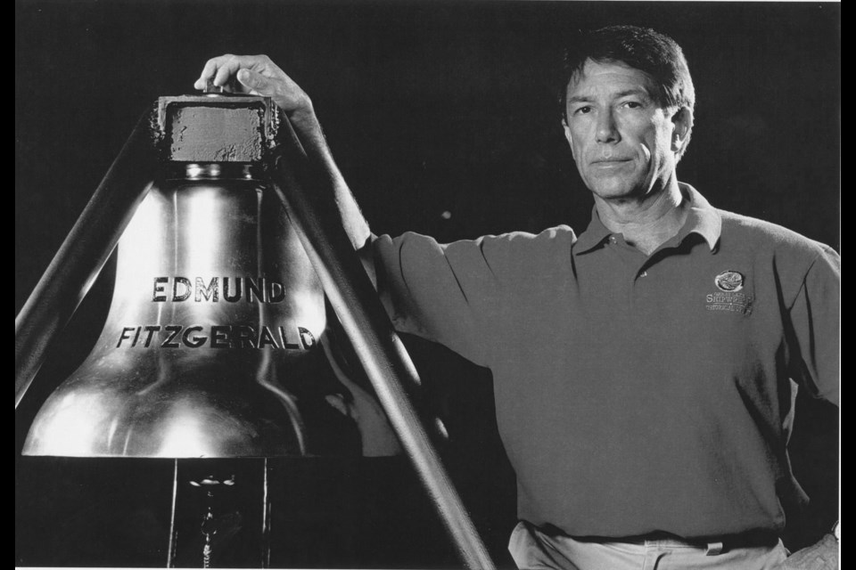 Tom Farnquist, beside the ships bell recovered from the Edmund Fitzgerald. Photo by Chris Winters, courtesy of Tom Farnquist. Photo provided