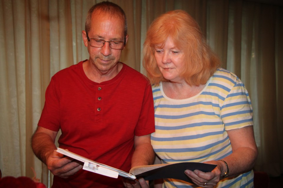 Dan Giddens and Kathy Millette of Sault Ste. Marie browse through a book of wartime memoirs written by their father Ron Giddens, August 16, 2016. Darren Taylor/SooToday