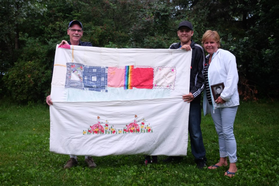 Stéphane Dosko lived with HIV for 17 years before passing away in 2007. (Left to Right) Dosko's husband Steve Miller, his nephew Justin Baxter, and his sister Tania Dosko hold 'The Quilt', a keepsake with a special message that Stéphane put together before he passed away. Photo by Jeff Klassen for SooToday