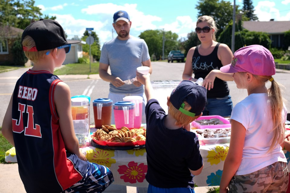 The Haynes family set up a Lemonade stand on Lake Street on Saturday, raising $310.50 for local charities. The parents said they were doing it to teach their kids about 'karma'. Photo by Jeff Klassen for Sootoday