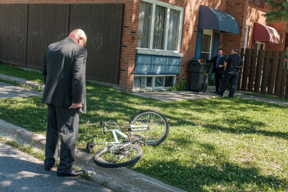Sault Ste. Marie City Police Service investigator examines a bike outside a home on Boston Ave. July 16. Jeff Klassen/SooToday
