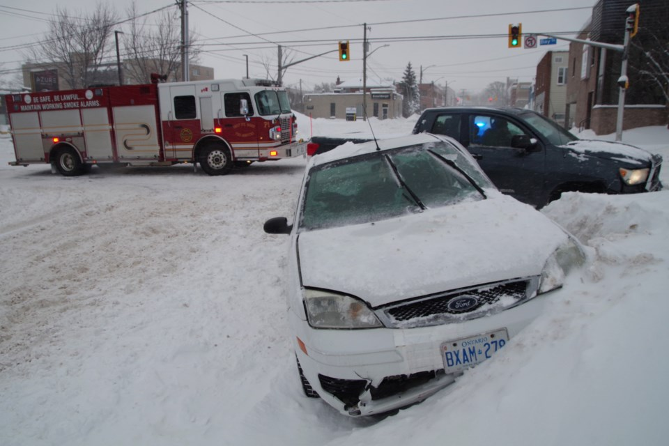 A white car is lodged in a snowbank following a collision at Spring and Bay this morning. Michael Purvis/SooToday