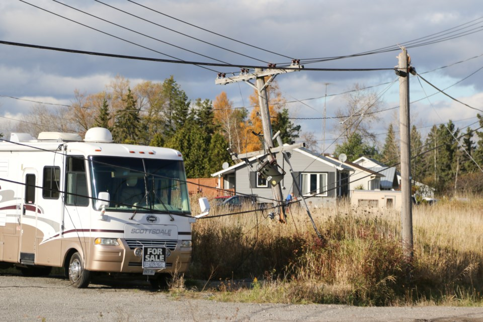 A truck hauling construction equipment snagged and pulled down a live power line on Black Road Sunday. Jeff Klassen/SooToday
