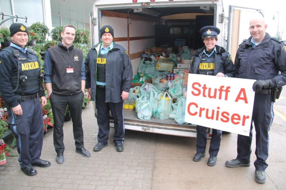 OPP auxiliary officers Steve Whitfield, Luke Elwgren, Ariella Arbus and Jeff Dewar with Chris Rome, Rome's Independent Grocer owner (second from left) at the annual OPP Stuff a Cruiser food drive at Rome's, Dec. 2, 2017. Darren Taylor/SooToday