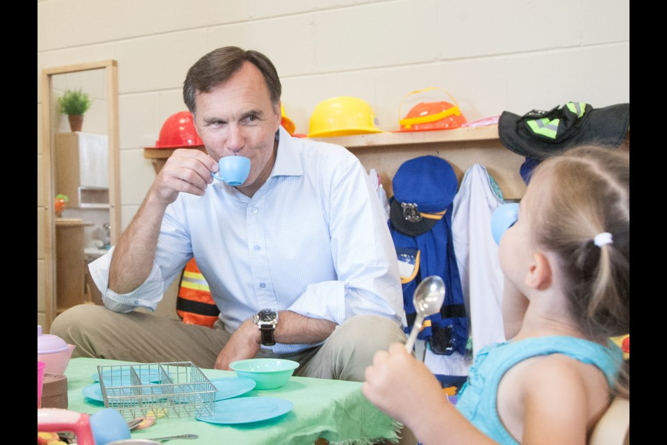 Federal Finance Minister Bill Morneau shares a cup of tea with Daniella Greco, age two, during a meet and greet August 10, 2016 at Early Years/Best Start Hub Holy Cross School. Kenneth Armstrong/SooToday