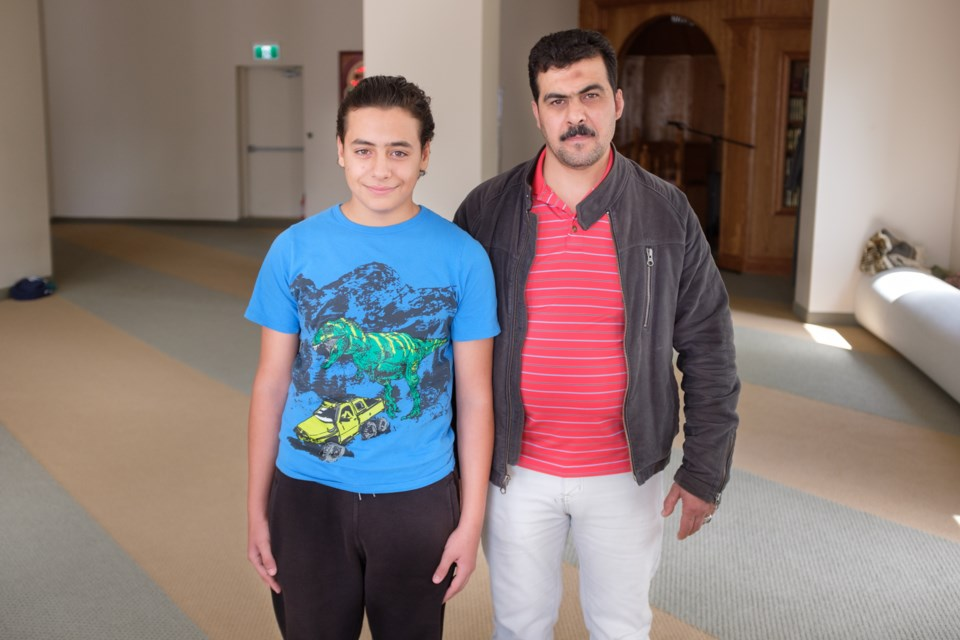 When Ahmad, 14, (left) left Damascus, Syria three years ago, Assad'€™s army was attacking his housing area and 23 people including his family had to cram into a four-person car to get away. Then he worked in Turkey for three years making jeans. He said he would have to work 18 hours days and only get 5 minute breaks. Ahmad'€™s father, Assam Talbiseh (right) is now a driver for the mosque. Jeff Klassen/SooToday