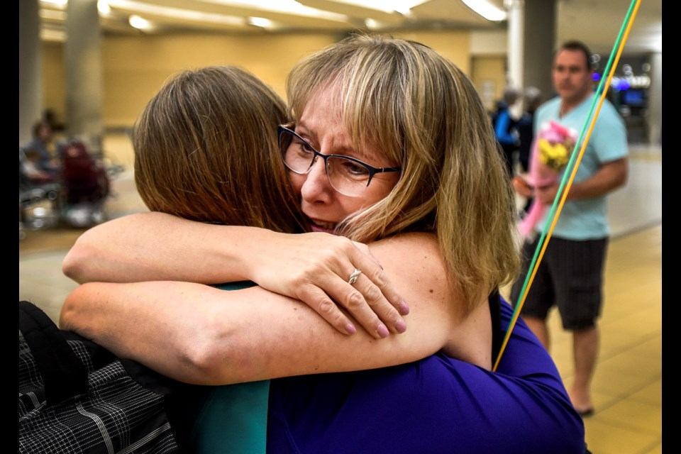 Velvet Martin of St. Albert, right, hugs her sister for the first time at the Edmonton International Airport on Tuesday.  Bonnie Williamson-Powell arrived from Ontario for a week-long visit with her newfound sister. DAN RIEDLHUBER/St. Albert Gazette