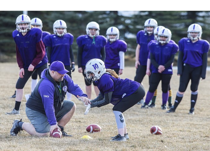 HELPING HAND – Assistant coach Geoff Richer demonstrates how to position the hands to receive a snap from centre to Charley Tourond of the St. Albert Valkyries at Wednesday's practice at Oakmont park. The Valkyries are one of four Capital District Minor Football Association teams competing in the inaugural six-on-six midget female spring league.
