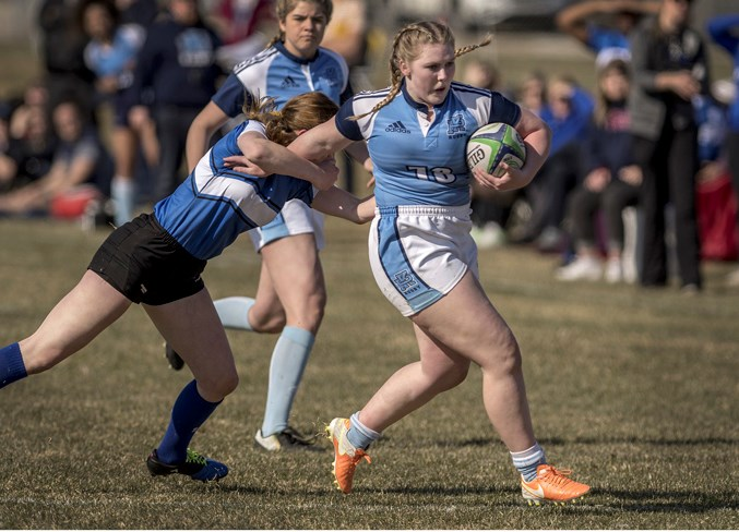 LEADING THE WAY – Calleigh-Ann Woodworth of the Paul Kane Blues slips a tackle from Angeline Sturko of the Harry Ainlay Titans in Tuesday's metro Edmonton division two women's match at St. Albert Rugby Football Club. In the background is Ainsley Maxwell of Paul Kane. Woodworth, an inside-centre, scored two tries and set up a third in the 29-5 victory. Paul Kane lost last year's final to Ainlay 27-12. The next match for Paul Kane is Tuesday against the Archbishop Jordan Scots and both teams are 2-0. Kickoff is 4:45 p.m. at Lynn Davies Rugby Park. DAN RIEDLHUBER/St. Albert Gazette