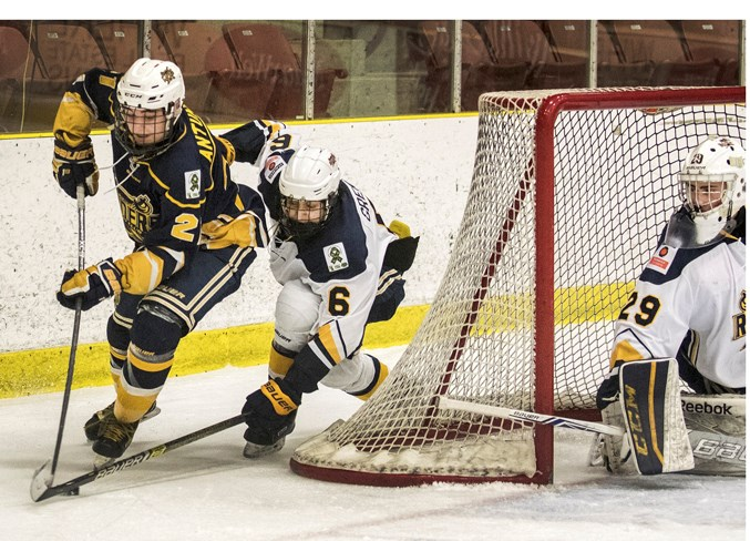 TURNING THE CORNER – Jayden Antunes, left, of the St. Albert Blues attempts a wrap-around against Tanvir Grewal and netminder Evan Hergott of the St. Albert Source for Sports Crusaders in Friday's playoff game in the Besa division of the Northern Alberta Midget AA Hockey League. The Crusaders won 6-3 at Go Auto Arena. The Blues finished pool play at 0-1-3 while Crusaders were 3-0-1 for a berth in Monday's semifinal against the PAC Saints. The Crusaders, the defending league champions and the top team this season at 26-4-2, defeated the Saints 4-2 at JRC Arena. DAN RIEDLHUBER/St. Albert Gazette