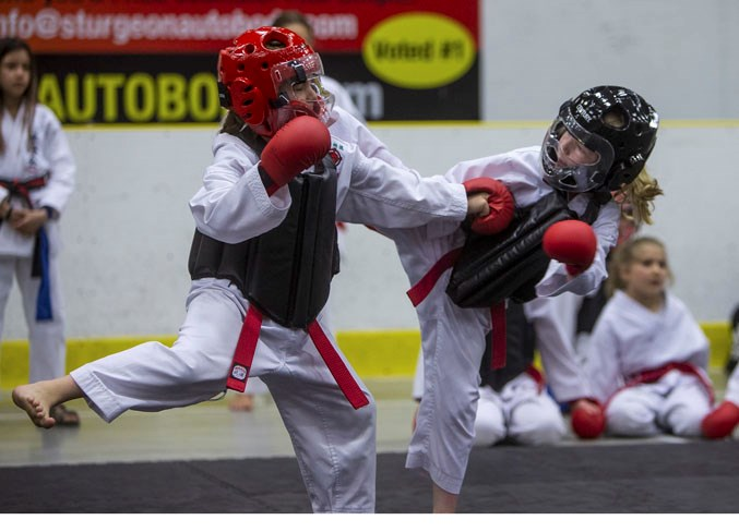 COMBATANTS – Evelyn Brown, left, and Annika Harris exchange strikes and kicks in the red belt female 6 to 8 sparring division at the 21st annual Spirit of the North, hosted by the Desa School of Karate at Servus Credit Union Place. The two-day event featured 280 competitors and 89 divisions in kata, kumite (sparring) and kobudo (weapons training) for ages six to adult from white belts to black belts.