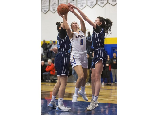 TWO ON ONE – Kyleigh Kornak of the St. Albert Skyhawks is double-teamed in the paint by Kayleena Garda, right, and Ella Stanley of the Paul Kane Blues in the metro Edmonton division one league. The 4A provincials tip off Thursday for both teams and in the round of 16, the No. 1-ranked Skyhawks (13-0 as repeat winners of the division one championship and 26-5 overall), host the No. 16 Charles Spencer Mavericks of Grande Prairie at 11 a.m. and the No. 10 Paul Kane Blues (9-3 in division one and 18-9 overall) welcome the No. 7 Magrath Pandas at 9 a.m. The remaining games for the Skyhawks and Paul Kane, including a second game on Thursday, will be played at Jasper Place High School. Visit www.asaa.ca for the provincial draw. CHRIS COLBOURNE/St. Albert Gazette