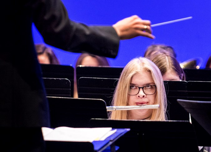 A member of the Sturgeon Composite High School band looks up at conductor Kyle Swenson as she plays a flute in the Concert Band competition of the annual Rotary Music Festival at the Arden Theatre in St. Albert on Wednesday, April 10.  DAN RIEDLHUBER/St. Albert Gazette