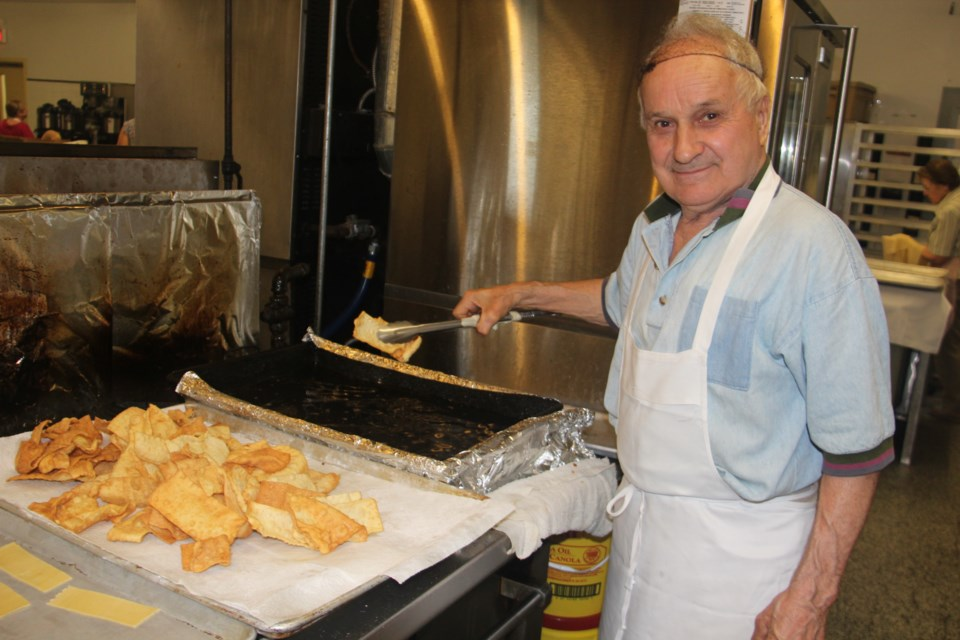 Kitchen volunteer Vittorio Guizzo deep fries some crostoli which will be sold at the 46th annual Società Caruso Italian Festival, which starts Thursday and runs to Sunday. (Heidi Ulrichsen/Sudbury.com)