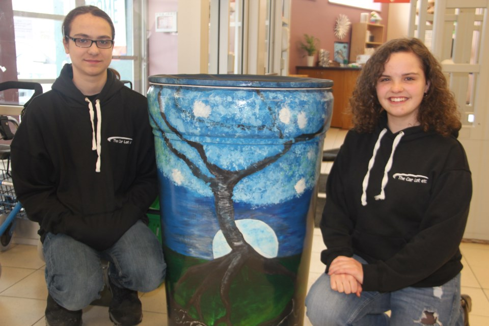Antoine Laroche and Kalem Mahaffy show off a painted rain barrel. The homeschoolers will be painting rain barrels for local community gardens. They received a $500 grant from Project Impact to help them with their initiative. (Heidi Ulrichsen/Sudbury.com)