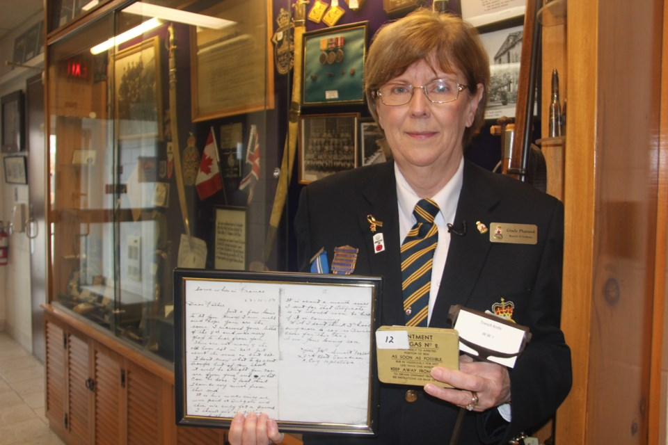 Gisele Pharand of Branch 76 of the Royal Canadian Legion shows off some of the First World War artifacts that are on display at the branch. This includes a letter from a soldier to his father, ointment for soldiers to apply after being gassed in the trenches and a trench knife, which helped them climb out of the trenches in an attack. (Heidi Ulrichsen/Sudbury.com)