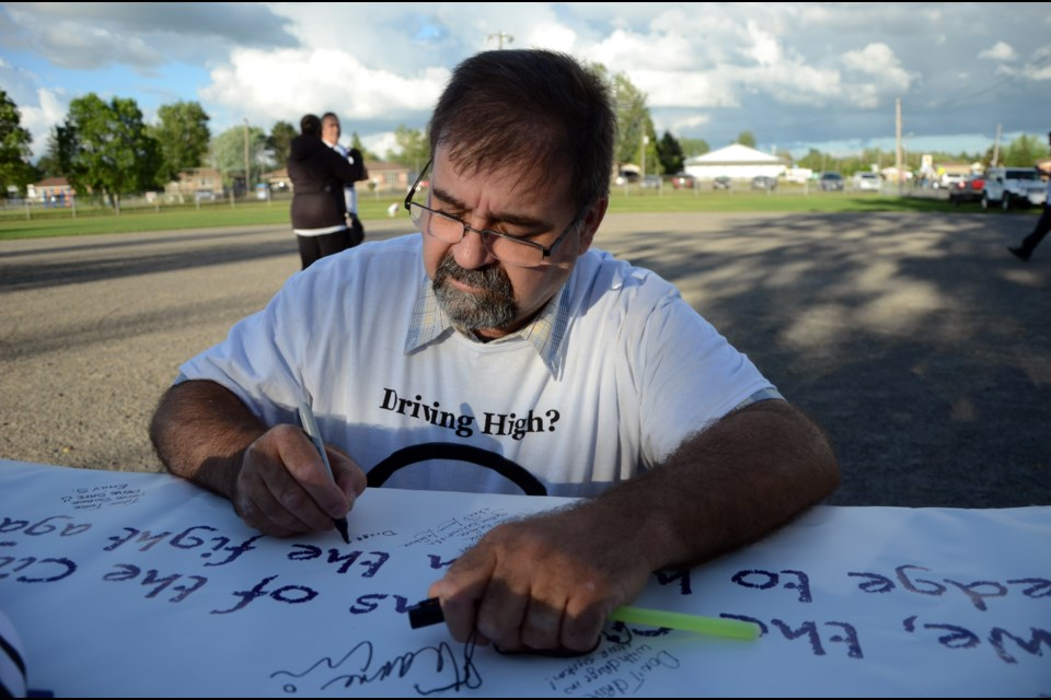 Gilles Lefebvre signs a banner prior to the start of the sixth memorial walk honouring the memories of Jazmine Houle, Steven Philippe and Caitlin Jelley. (Arron Pickard/Sudbury.com)