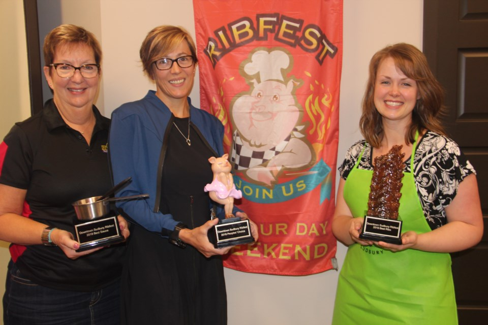 (From left) Downtown Sudbury executive director Maureen Luoma, YMCA of Northeastern Ontario president and CEO Helen Francis and reThink Green communications director Leigha Benford show off the Ribfest Sudbury trophies. (Heidi Ulrichsen/Sudbury.com)