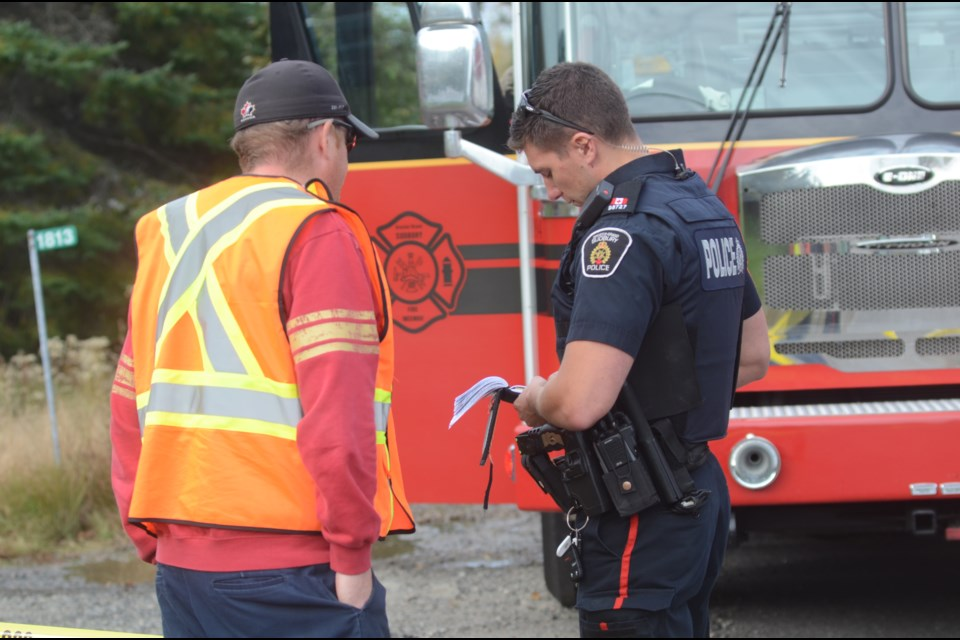 A police officer speaks with a resident of the neighbourhood where the fire occurred. (Arron Pickard/Sudbury.com)